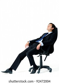 Corporate worker in business suit leans back on his office chair, daydreaming about his upcoming vacation
