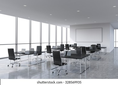 Corporate workplaces equipped by modern laptops in a modern panoramic office, white copy space in the windows. Black leather chairs and a black tables, a huge whiteboard on the wall. 3D rendering.