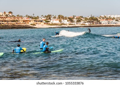 Corralejo, Fuerteventura, Canary Islands, Spain - February 17, 2018: Surfers in the beach of Corralejo Bay at morning