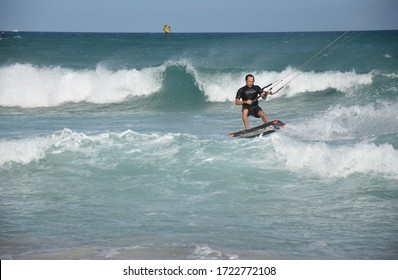 Corralejo, Fuerteventura - Oct, 3, 2019: Kitesurfer riding large waves doing jumps and tricks. Canary Islands.