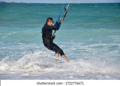 Corralejo, Fuerteventura - Oct, 4, 2019: Close up of a kitesurfer riding large waves with splashing water and spray.