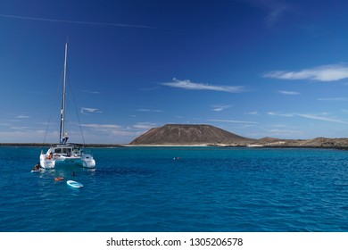 Corralejo, Fuerteventura / Spain - 11 11 2017: Catamaran stopped near the Lobos Island in the Canary Islands with cristal blue water with a paddle and a volcano in the background