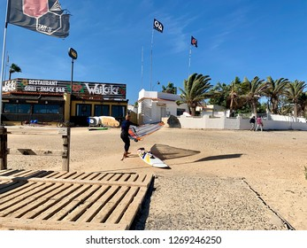 Corralejo, Fuerteventura / Spain - december 23, 2018. Wind surfer with a sail and a board on the beach. Windsurfer and equipment for windsurfing, Corralejo beach, windsurfing on the Feurteventura.