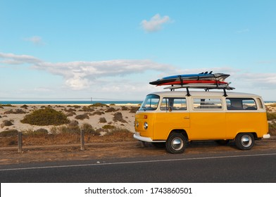 Corralejo, Fuerteventura/Spain - April 16 2019: Yellow Volkswagen Van, with coloured surfboards on the roof, next to Corralejo Beach on a sunny day