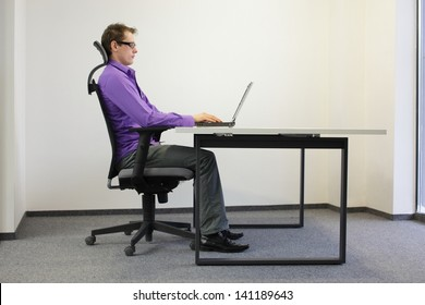 correct sitting position at workstation. man on chair working with laptop