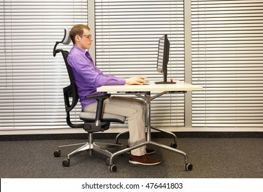 correct sitting position at workstation. man on chair working with computer