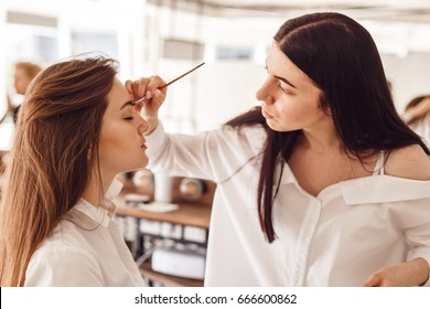 Correction of eyebrow tweezers, eyebrow henna painting, beautiful young girl beauty salon, perfect eyebrows. Professional care for face.