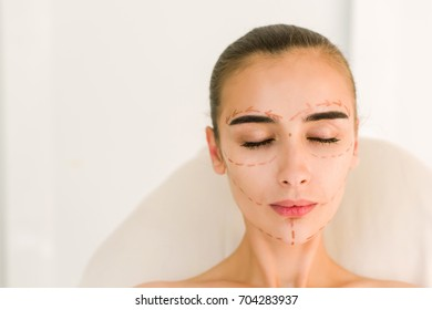 Correction lines on woman face. Attractive girl with dark eyebrows and naked shoulders at white background. Closed eyes.