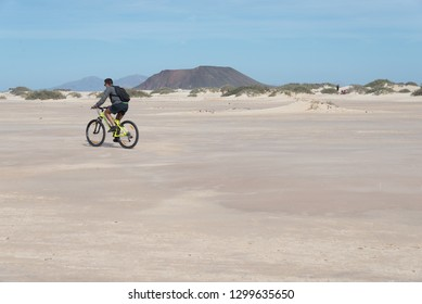 Correlate, Fuerteventura ; 01 02 2017: Cycling in the Dunes National Park beach in Corralejo with Lobos's Island background, in Fuerteventura , Canary Islands, Spain