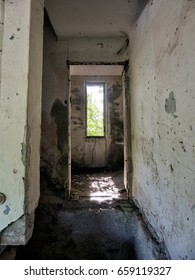 Corridor in abandoned, rundown property, former house. Derelict now with peeling paint and debris.