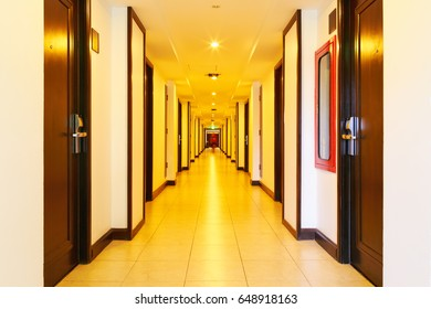 Corridor between hotel rooms with wireless internet transceiver or router on ceiling and blurry people walking to their room