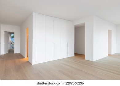 Corridor with built-in wardrobes, white walls and parquet. Nobody inside