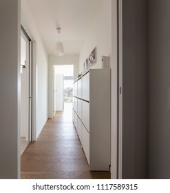 Corridor with chest of drawers and city view. White walls