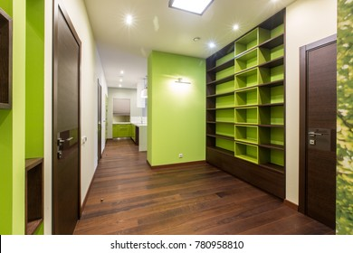 The corridor in green-brown tones, in which there are cabinets with shelves and a passage to the kitchen