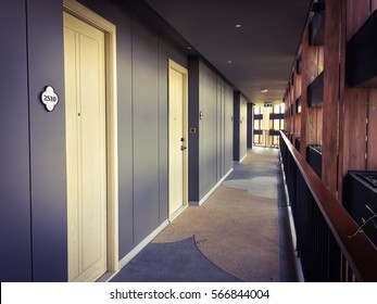 Corridor in hotel building with apartment rooms and windows, grey walls and beige doors