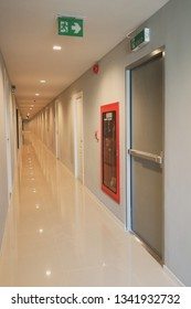 The corridor inside the apartment building has signs and fire escape doors in the building.