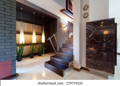 Corridor with metal and wooden stairs in modern interior