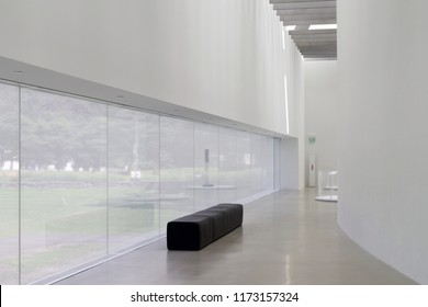 Corridor of modern, clean art gallery or museum with large white walls.