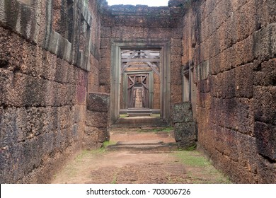 Corridor of Stone Walls and Ancient Trees close to a Wood Door in Siem Reap Angkor Wat Temple Cambodia Asia