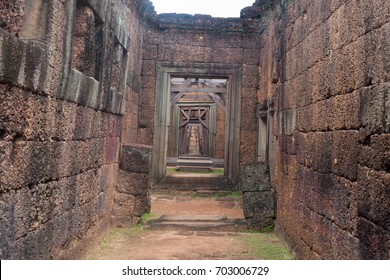Corridor of Stone Walls and Ancient Trees close to a Wood Door in Siem Reap Angkor Wat Temple Cambodia Asia Tomb Raider