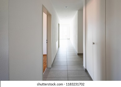 Corridor with tiles, fitted wardrobes and open doors. Nobody inside