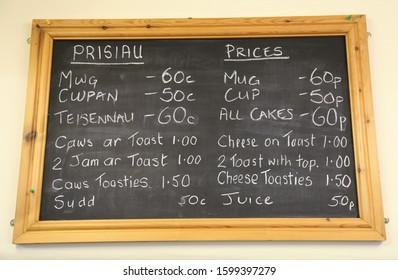 Corris, Gwynedd, Wales, UK.  December 3, 2019. A bilingual, pine framed chalk board displaying prices in a Welsh Tea Room
