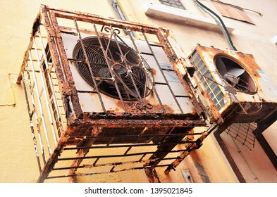 Corroding air-conditioners hanging in the street
