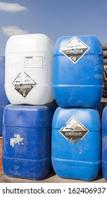 Corrosive, destroys living tissue on contact, hazard symbol or warning sign on plastic cans warning not to expose skin to substance