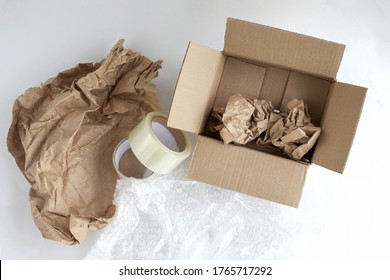 Corrugated box. Duct tape, paper for packaging inside the box. Bubble wrap. Tools for packaging products on a white background. Packer.