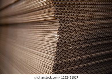 Corrugated cardboard sheets are one by one, they are prepared for the production of cardboard boxes. Polygraphic background of cardboard