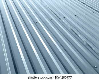 corrugated grey metal sheets with rivets on roof of industrial building
