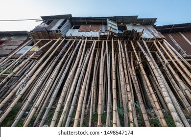 A corrugated iron riverside home raised on bamboo stilts to avoid flood waters in an Asian city.