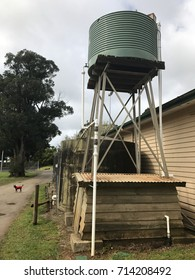 Corrugated iron water tank on stand in Australian rural township (with small dog)