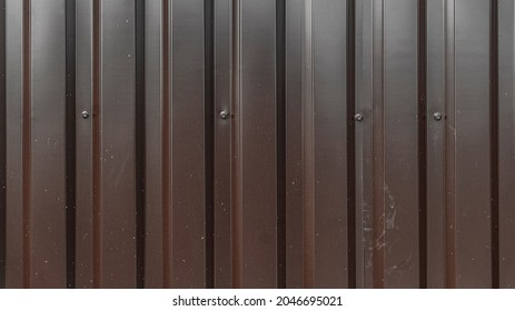 Corrugated metal sheet texture background. Texture of brown metal profiled sheet fence decking. Facing wall or roofing building material intended for use in construction in the construction. Ral 8017