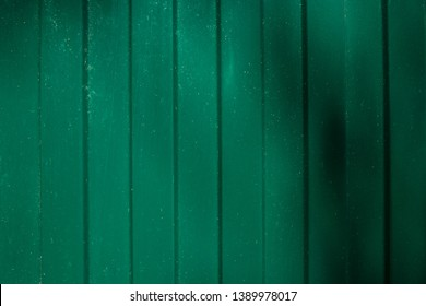 Corrugated metal wall background of green fence with shadows. Copy space