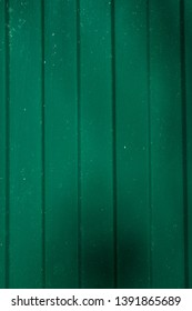Corrugated metal wall background of green fence with shadows. Vertical shot. Copy space