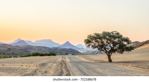 A corrugated road stretching away to some spectacular scenery of distant mesas and buttes, against an evening sky, Damaraland, Namibia.