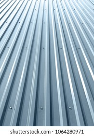 corrugated shiny metal plates on industrial building roof with rivets and bolts