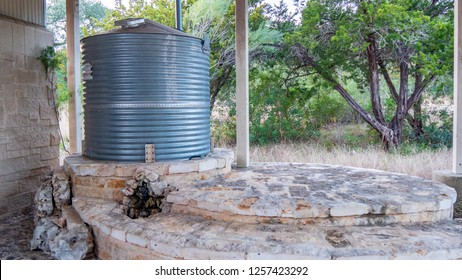 Corrugated steel water storage tank on top of flagstone masonry structure, with small stone fountain in front
