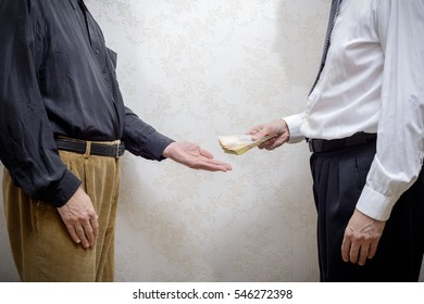 Corrupted businessman, or politician, paying a Hryvnia banknotes bribe to a man accepting corruption, in Ukraine
