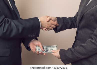 Corrupted businessman sealing the deal with a handshake and receiving a bribe money