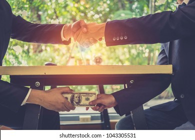 Corrupted two businessman sealing the deal with a handshake and receiving a bribe money. Hands passing money under table corruption bribery.