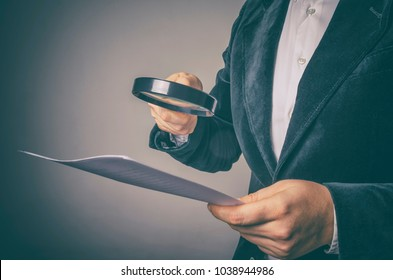 Corruption audit concept. The inspector uses a magnifying glass for inspecting budget corruption.