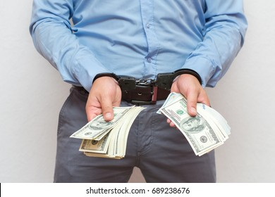 Corruption and bribery concept - arrested official with money in hands on white background