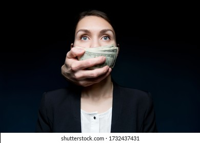 Corruption and bribery cover the woman s mouth with money. Business woman looking into the void, dollars are pressed to her mouth by hand from the dark