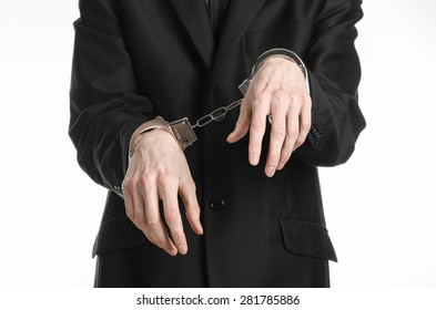 Corruption and bribery theme: businessman in a black suit with handcuffs on his hands on a white background in studio isolated