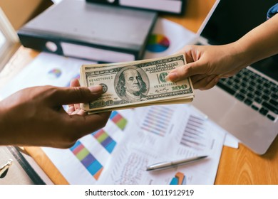 corruption concept.Man offering batch of hundred dollar bills. Hands close up. Venality, bribe,United States Dollars (USD).women Hand giving and receiving money from businessman.