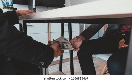 Corruption concept , Two businessmen giving money under table