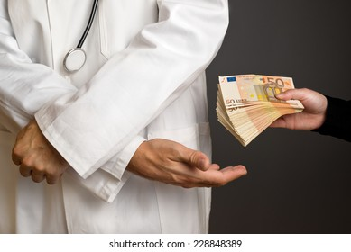 Corruption in Health Care Industry, Doctor receiving large amount of Euro banknotes as a bribe.
