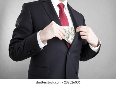 Corruption. Man putting money in suit jacket pocket.